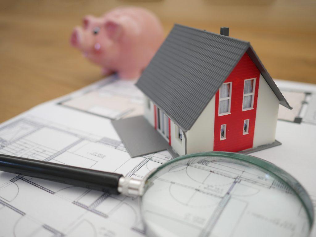 Figurine maison posée à côté d'une tirelire en forme de cochon