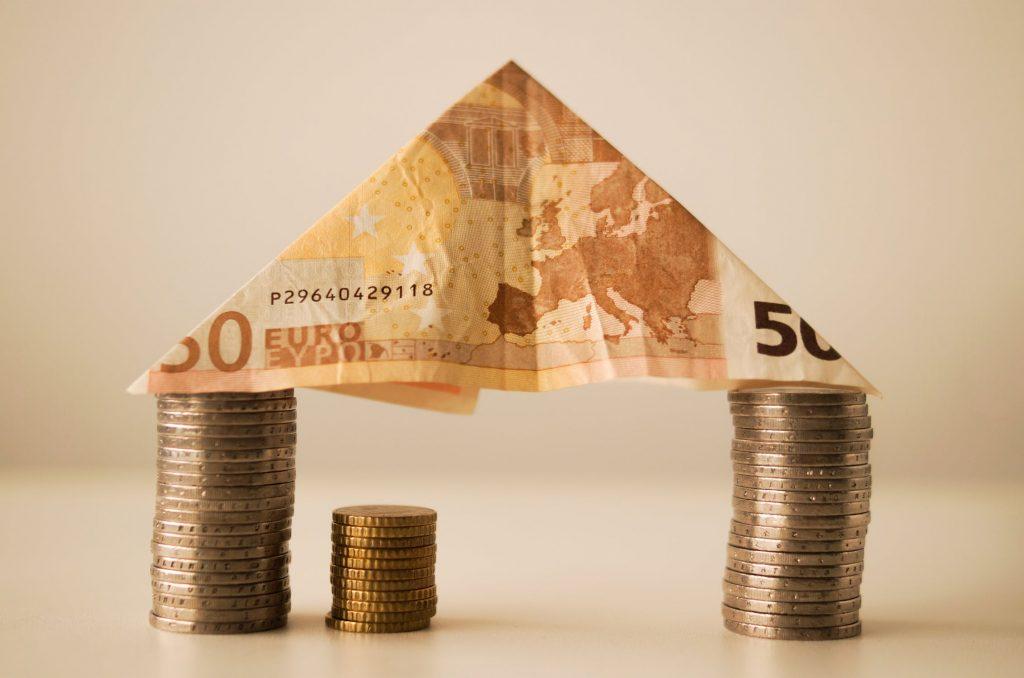 Maison fabriquée avec des pièces et des billets pour financer un projet immobilier