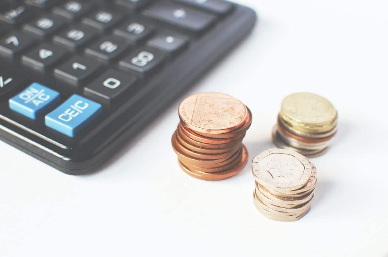 tas de pièces à côté d'une calculatrice